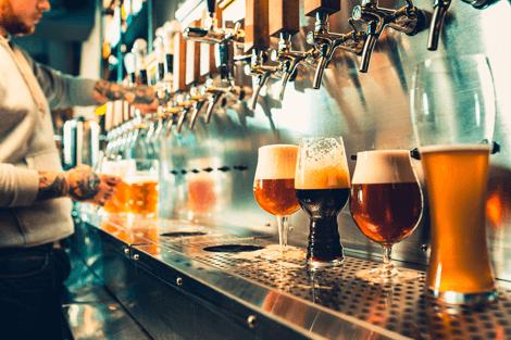 Barkeeper steht bei Bierzapfanlage und zapft verschiedene Biere