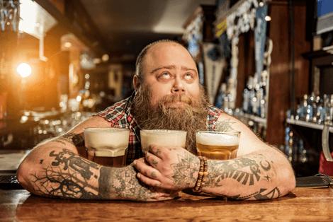Mann mit drei unterschiedlichen Bieren frisch aus der Bierzapfanlage